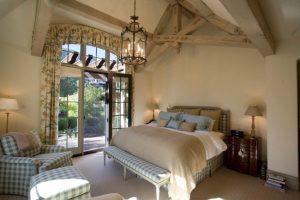 Кованая люстра в центре комнаты с лампами в форме свечей – изюминка интерьера спальни