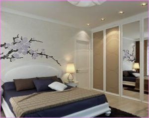 Данная спальня украшена рисунком на обоях и потрясающим светильником