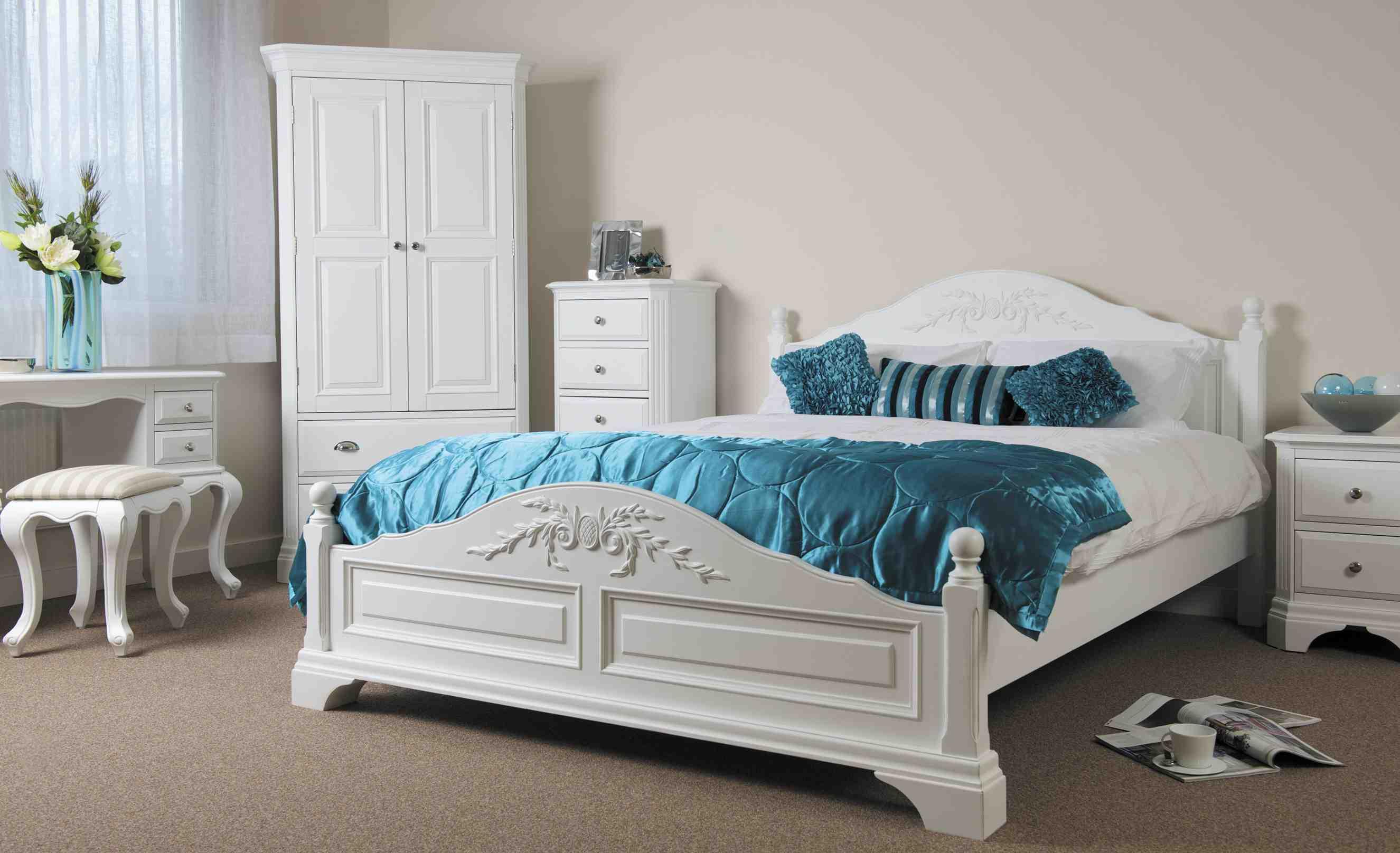 Белая кровать с бирюзовыми подушками