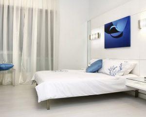 Белая спальня с телевизором в изголовье