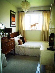 Спальня с кроватью комодом и прикроватной тумбой