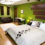 Интерьер просторной спальни в зеленом оформлении