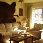 Интерьер уютной спальни со шкурами животных на стене
